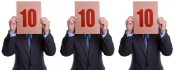 Three men in suites each holding up the number 10 indicating a perfect 10 score