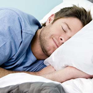 Man laying on pillow sleeping with a smile