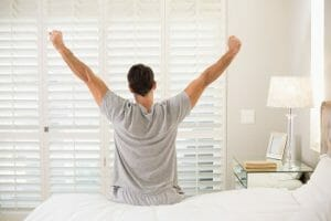 Man waking up refreshed. Sitting on edge of bed stretching arms out.