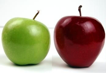 Green apple next to red apple comparing the two