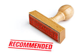 "Red ""recommended"" word with rubber stamp laying next to it"