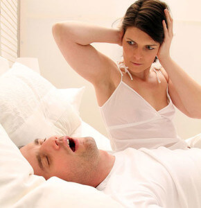 Woman holding ears with man snoring