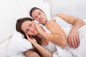 Woman covering ears laying next to snoring man