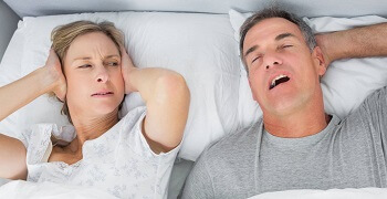 man snoring in bed next to woman
