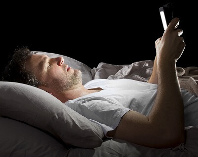 Man laying in bed looking at smart phone in dark