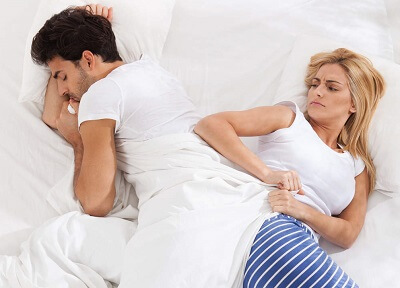 Wife pulling covers off husband